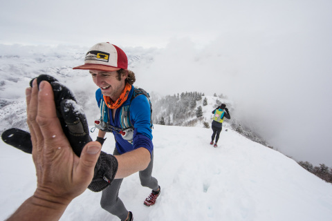 Man giving a high five at the top of a steep snowy mountain hill